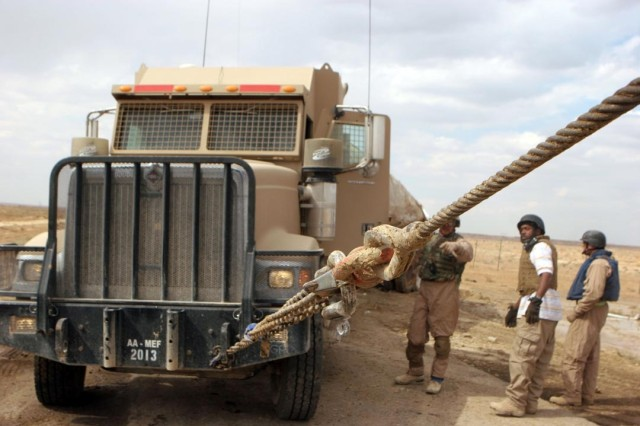 Contractors tow a vehicle out of a ditch in Asr Uranium, Iraq, March 29. The vehicle was recovered during a combat patrol to Camp Korean Village.