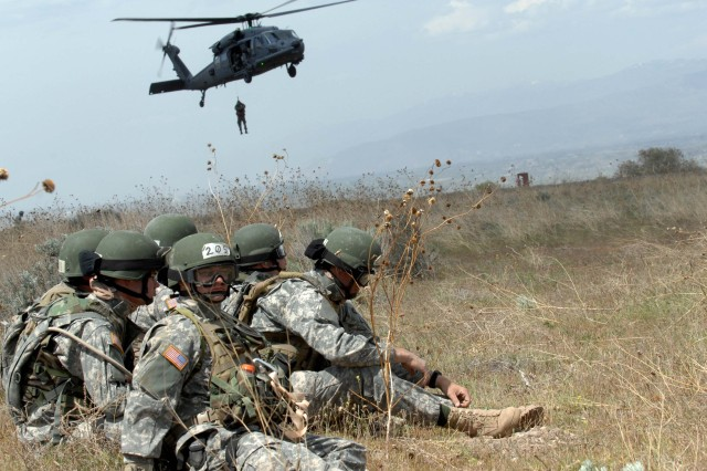 Soldiers wait to be hoisted aboard an Air Force HH-60 Pave Hawk helicopter.