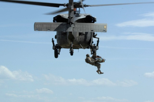 Soldiers are lifted aboard an Air Force HH-60 Pave Hawk helicopter.