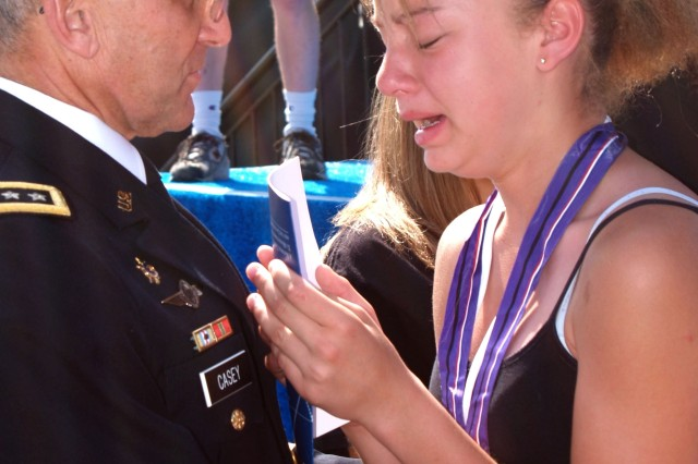 """Gen. George W. Casey Jr., Army chief of staff, consoles a young girl during the """"Time of Remembrance"""" ceremony, May 20."""