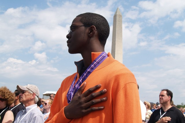 """Quincy Jallah, son of a fallen Soldier, honors the presentation of colors during the """"Time of Remembrance"""" ceremony today near the Washington Monument."""