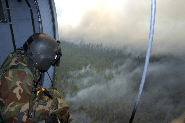 Sgt. Simon Debran looks out from a UH-60 Black Hawk helicopter May 16, during a mission to drop water onto wildfires raging in New Jersey.
