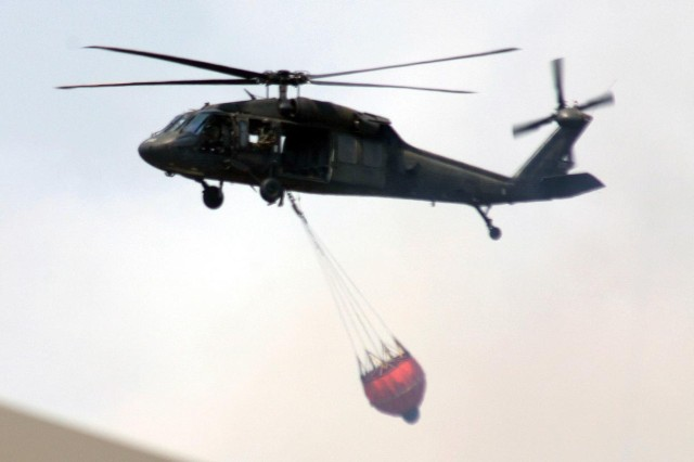 The Black Hawk helicopter prepares to dump water onto the New Jersey wildfires. The National Guard is helping firefighters contain the fires that have razed more than 12,000 acres of pinelands.