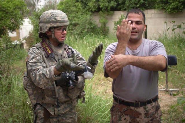 """Sgt. Tierney Nowland teaches the """"Macarena"""" (a type of dance) to an Iraqi Soldier during a break from a cordon and search mission in Ameriyah, May 16. She is a combat cameraman with the 982nd Signal Company."""