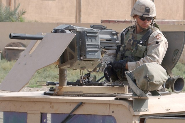 A military police Soldier provides security with his MK19-3 40mm grenade machine gun while seated in the turret of his humvee. The Soldier is assigned to the 4th Infantry Division's 4th Military Police Company. The unit provided an escort for Soldiers of the 230th Finance Battalion and the 443rd Civil Affairs Battalion, who were overseeing the Iraqi Currency Exchange in Balad, Iraq. U.S. Army photo by Sgt. Jack Morse.
