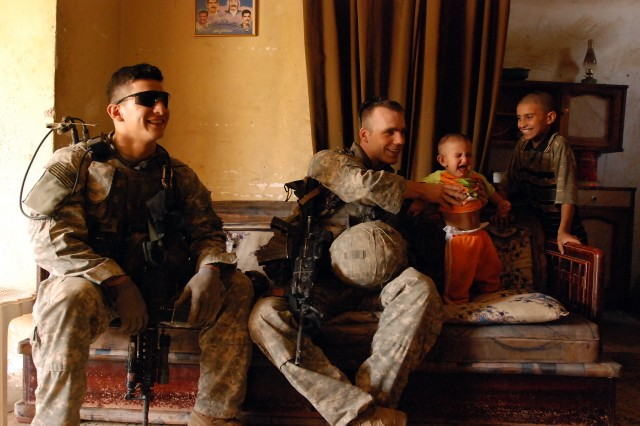 Sgt. John Reed (right) doesn't get the reaction he was hoping for while playing with a baby boy during a stop at an Iraqi family home while on patrol in east Baghdad's Sha'ab neighborhood May 8. Sgt. Reed and Sgt. Unberto Espinoza (left) are both with Company B, 2nd Battalion, 325th Airborne Infantry Regiment, 2nd Brigade Combat Team, 82nd Airborne Division.