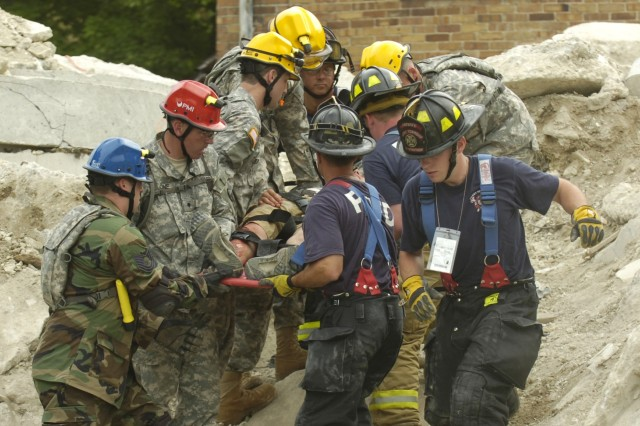 Soldiers move the simulated victim to a medical facility.