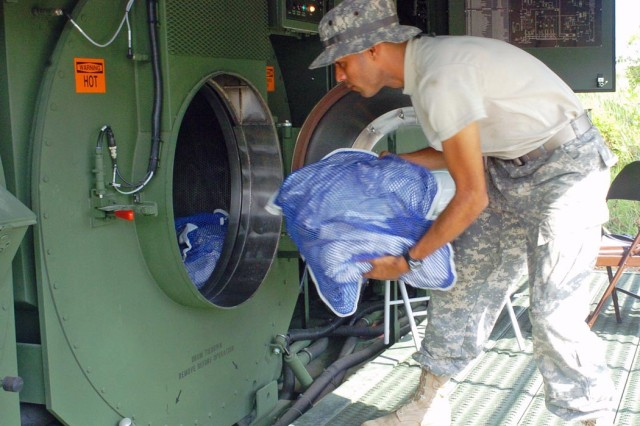 Spc. Angel Rivera loads a bundle of laundry into the Laundry Advanced System during Tradewinds 2007.