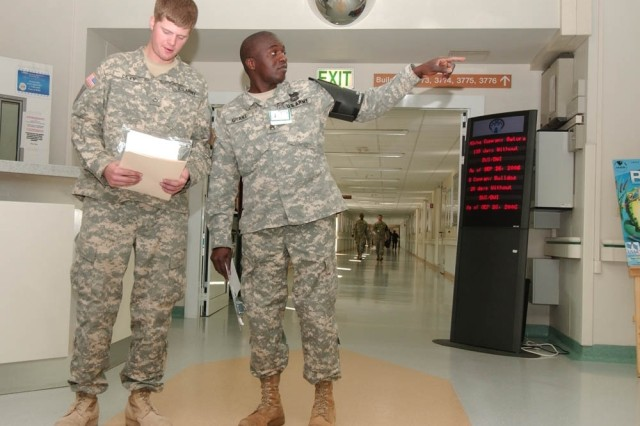 Staff Sgt. Darold Grant, Landstuhl Regional Medical Center patient liaison officer, directs Pfc. Kade Levy, Company C, 1st Battalion, 18th Infantry Regiment, 1st Infantry Division, to a medical appointment.  Grant and other LNOs ensure that wounded warriors under their care know when and where their medical appointments take place.