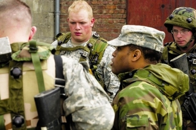 Sgt. 1st Class David Williams (in soft cap), first sergeant for USAG Schinnen and training NCOIC at the Camp Roi Albert MOUT site, does a quick after-action review with Soldiers who completed their first attempt at clearing buildings May 17, 2007, during Warrior Week.
