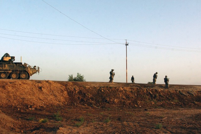 Soldiers search the area near the site of the IED detonation.