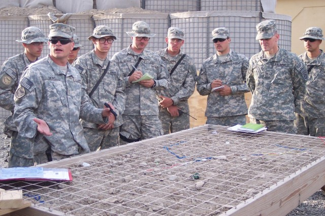 2nd Lt. John Deal, a platoon leader, explains mission details using a sand table, as Brig. Gen. Joseph Votel and fellow Soldiers look on.