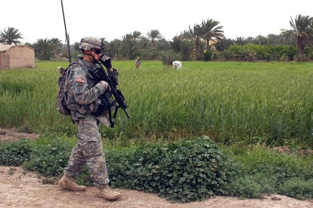 An Iraqi farm family works in the fields as Sgt. Sean Reed, a team leader with 1st Squadron, 40th Cavalry Regiment, 4th Brigade Combat Team (Airborne), 25th Infantry Division, walks past during a reconnaissance patrol in Adwaniya.