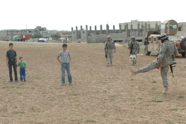 Soldiers with the 27th Brigade Support Battalion take time to play with the children on the soccer field in Al Kosh, Iraq, while on a humanitarian mission May 19. During the Soldier's visit to the village, they handed out new baseball uniforms, helmets, bats and hats, as well as blankets for the local citizens. (U.S. Army photo by Pfc. Bradley Clark, 4th BCT, 1st Cav. Div. Public Affairs)