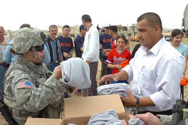 Civil Affairs officer, 1st Lt. Kendra Evers, 27th Brigade Support Battalion, 4th Brigade Combat Team, 1st Cavalry Division, helps hand out new uniforms to the boys and girls softball teams in Al Kosh, Iraq, during a humanitarian mission May 19. (U.S. Army photo by Pfc. Bradley Clark, 4th BCT, 1st Cav. Div. Public Affairs)