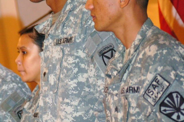 Soldiers wait to be greeted by naturalization ceremony attendees.