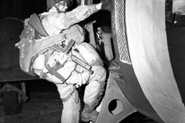 A paratrooper boards an airplane that will drop him over the coast of Normandy for the Allied Invasion of Europe, D-Day, June 6, 1944. Soldiers of the 82nd and 101st Airborne Divisions parachuted behind enemy lines during the night, while fellow Soldiers assaulted Normandy beaches at dawn.