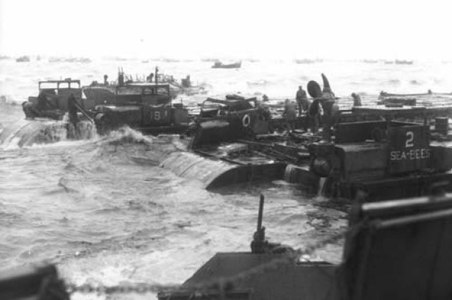 Barges carrying supplies for Soldiers are challenged by pounding surf along the Normandy coast, D-Day, June 6, 1944.