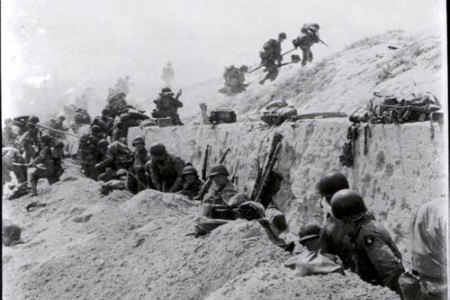 Soldiers move over a seawall on Utah Beach during the Allied Invasion of Europe.