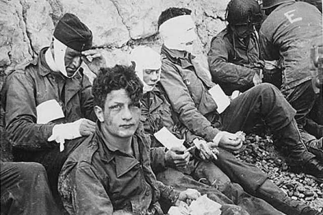 Soldiers of the 16th Infantry Regiment, wounded while storming Omaha Beach, wait by the chalk cliffs for evacuation to a field hospital for treatment,  D-Day, June 6, 1944.