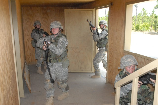 Mini-BCT participants from several marketing companies that promote the Army work as a four-member team as they prepare to enter an unsecured building at the military operations on urbanized terrain site.