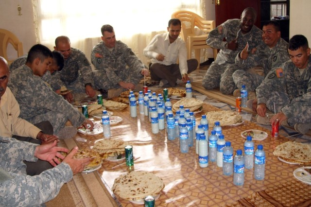 Soldiers from 2nd Battalion, 35th Infantry Regiment, 3rd Brigade Combat Team, 25th Infantry Division, share a meal hosted by a tribal leader in the village of Hasary Gawra in the Altun Kapri District of Kirkuk, Iraq, May 9.