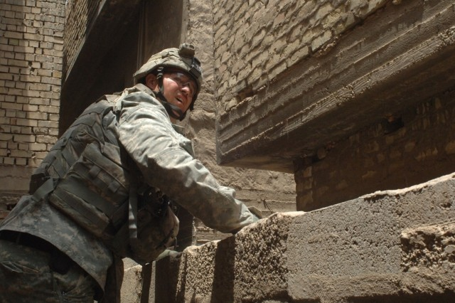 A Soldier peers over a wall before climbing over.