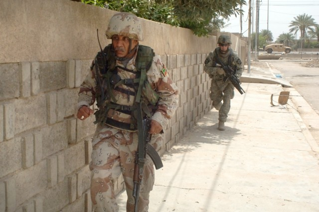 Sgt. Jesse McDowelland and an Iraqi Soldier use a wall as cover as they move quickly to their next objective.