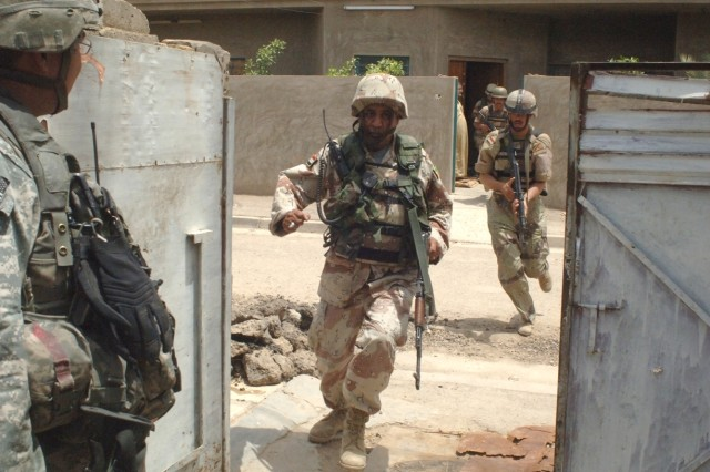 Iraqi Soldiers rush through an opening in a wall to another house as a U.S. Soldier provides security for them.