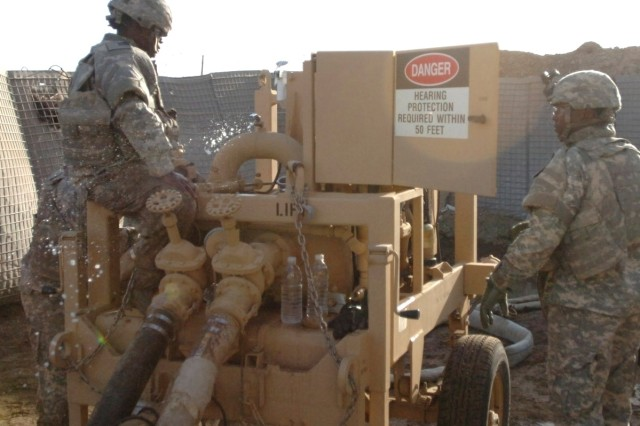 Sgt. Tanesha Carn (left), a petroleum supply specialist, and Staff Sgt. Damon Walker, a truck driver, repair a water pump at the Karkh Water Treatment Repair Plant in north Baghdad on May 8. The Soldiers are from Company A, 115th Brigade Support Battalion, 1st Brigade Combat Team, 1st Cavalry Division.