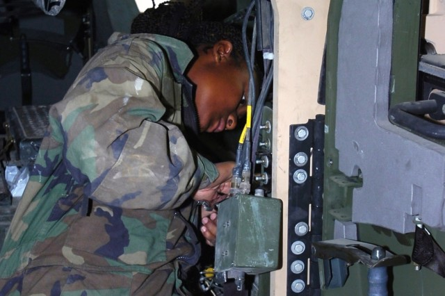 Spc. Natasha Marshall, an air conditioning mechanic for the 3rd General Support Aviation Battalion, 82nd Combat Aviation Brigade, installs bolts to secure an up-armored door on a Humvee at Bagram Airfield, Afghanistan, May 25.