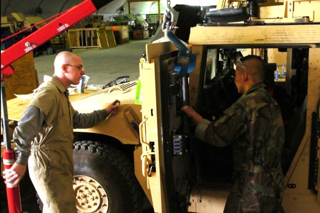 Pfc. Joshua Bullard and Sgt. Kang Hoon Lee, both mechanics with the 122nd Aviation Support Battalion, 82nd Combat Aviation Brigade, use a hoist to install an up-armored door on a Humvee at Bagram Airfield, Afghanistan, May 25.