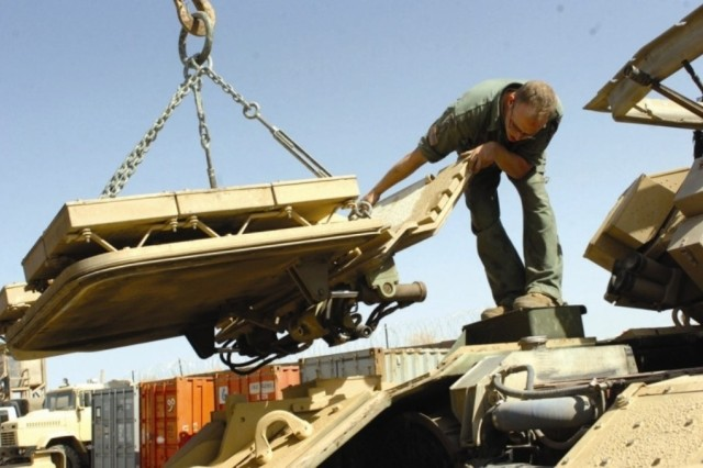 Spc. Kurt Scheidenberger, from Troop A, 1st Squadron, 9th Cavalry Regiment, 4th Brigade Combat Team, 1st Cavalry Division, works on a Bradley Fighting Vehicle May 16 in Mosul, Iraq. The hood to the vehicle was removed to pull the engine.