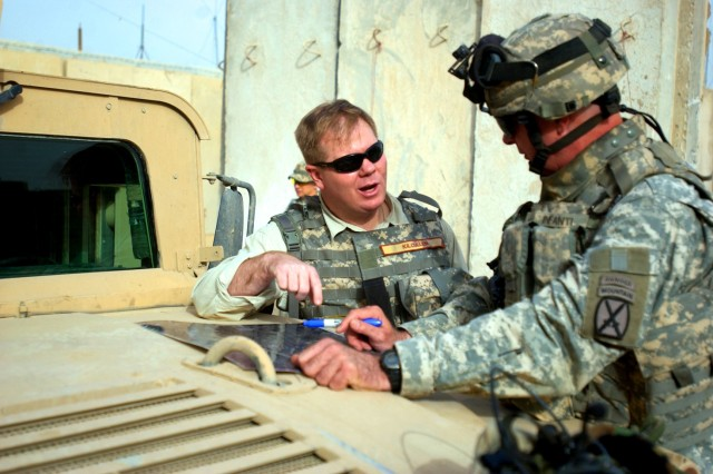 Dr. David Kilcullen (left) asks a question of Lt. Col. Michael Infanti, commander of the 4th Battalion, 31st Infantry Regiment, 2nd Brigade Combat Team, 10th Mountain Division (Light Infantry) out of Fort Drum, N.Y., before visiting the Yusufiyah, Iraq Joint Security Station June 3. Dr. Kilcullen, counterinsurgency adviser to Gen. David Petraeus, commander of U.S. Forces in Iraq, visited much of the 2nd BCT's area of operations June 2 and 3.