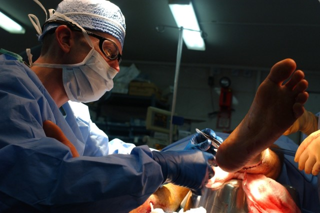 A surgeon from the 28th Combat Support Hospital treats a wounded Soldier at Camp Marez in Mosul, Iraq.