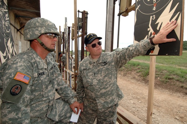 Chief Warrant Officer 4 Bryan Wood, right, B Co., 6th Battalion, 52nd Aviation Regiment, Fort McCoy, Wisc., who has been a match shooter since the 1960s and is a member of the President's One Hundred, talks about the finer points of shot groupings with Sgt. 1st Class Carl Krause, 157th Infantry Brigade, Fort Jackson, S.C.