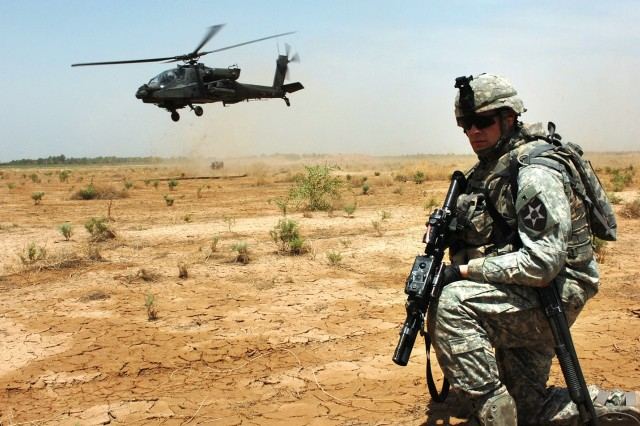 Spc. Thomas Quinn pulls security as an AH-64D Apache helicopter takes off.