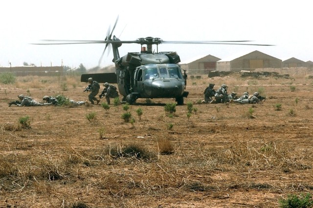 Soldiers exit a UH-60 Black Hawk helicopter.