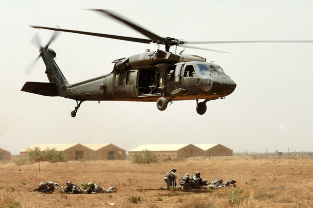 Soldiers take up defensive positions after exiting a UH-60 Black Hawk helicopter.