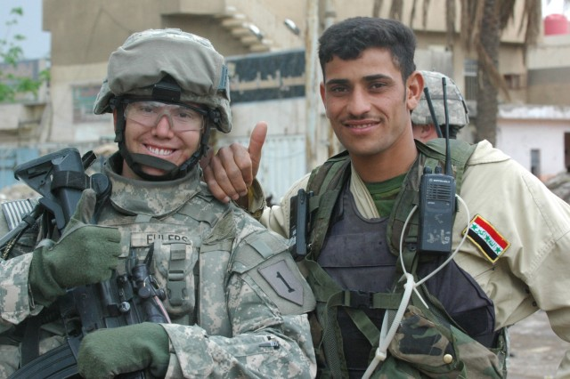1st Lt. Mark Ehlers, the leader of 1st Platoon, Troop B, 1st Squadron, 4th Cavalry Regiment, makes friends with an Iraqi National Policeman from 1st Battalion, 6th National Police Brigade during a patrol in the Saha neighborhood of southern Baghdad.