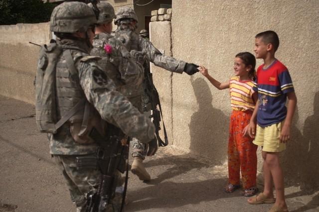 Iraqi children greet the Soldiers.