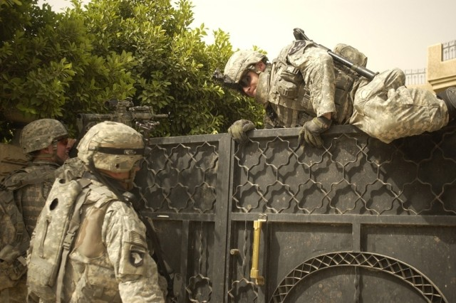 A Soldier climbs over a gate to unlock it for fellow Soldiers during the search for insurgents.