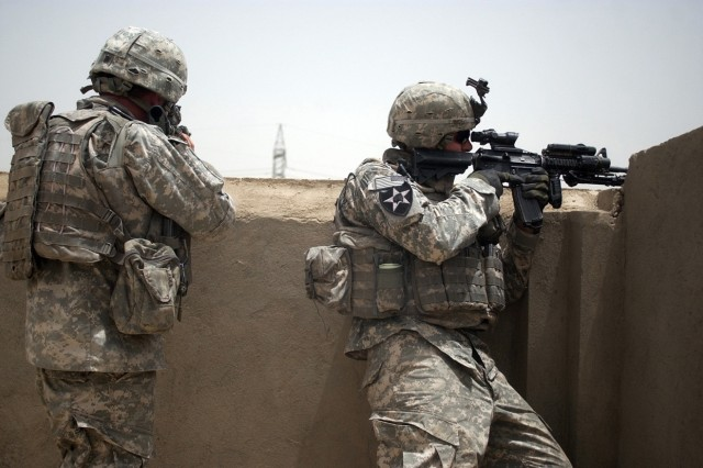 Sgts. Matthew Caulifield and Andrew Britt look for targets during the firefight.