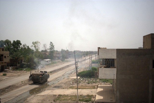 Smoke rises from the firefight as Soldiers in their Stryker vehicle and on rooftops engage insurgents.