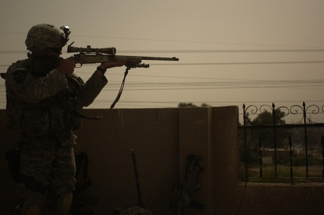 A sniper searches for insurgents from a rooftop as darkness falls.