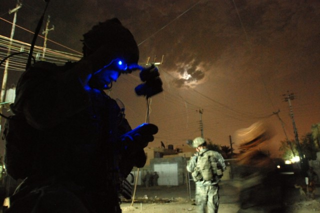 Sgt. Robert Brogdon, a squad leader with Company B, 2nd Battalion, 325th Airborne Infantry Regiment, 2nd Brigade Combat Team, 82nd Airborne Division, checks his position using GPS while conducting a nighttime foot patrol in Sha'ab, Baghdad, May 4.