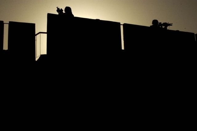 Soldiers pull security on a rooftop during a combined cordon and search mission with Iraqi police in the Rashid district of Baghdad, May 6. The Soldiers are from Company B, 1st Battalion, 23rd Infantry Regiment, 3rd Stryker Brigade Combat Team, 2nd Infantry Division.