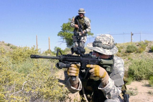 1st Sgt. Jason Riley, of the New Mexico National Guard's Combat Arms Training Company, takes up a firing position on a live-fire obstacle course during training in the New Mexico National Guard's gunfighter course near Albuquerque, N.M., May 30.