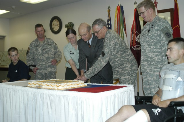 Spc. Andrew Hanson (left), Sgt. Maj. Of the Army Kenneth O. Preston, Pvt. Olivia Dexter (Walter Reed's youngest Soldier), Acting Secretary of the Army Pete Geren, Col. Ronald West (Walter Reed's oldest Soldier), Maj. Gen. Eric B. Schoomaker, commanding general of the North Atlantic Regional Medical Command and Walter Reed Army Medical Center, and Pfc, Ian Gillis, cut a cake Tuesday celebrating the Army's 232nd birthday at Walter Reed Army Medical Center.