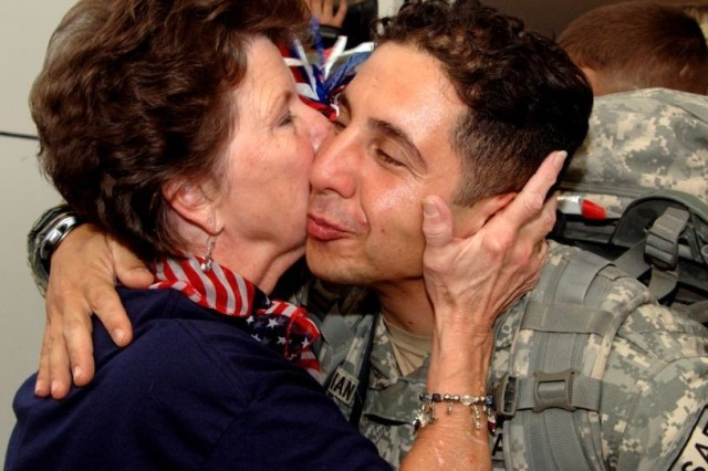 Linda Tinnerman kisses a Soldier returning from operations Iraqi Freedom and Enduring Freedom at the Dallas/Fort Worth Airport during a celebration of the R&R programAca,!a,,cs half-millionth traveler.